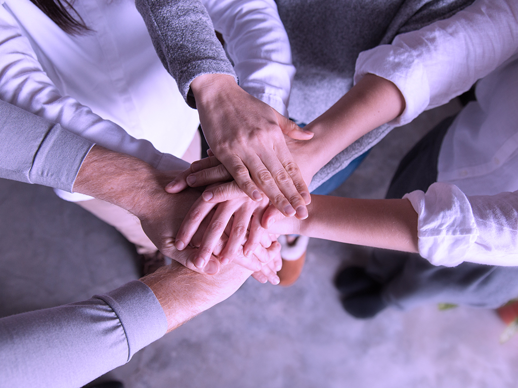 A group of people bringing their hands in together to emphasise on team building